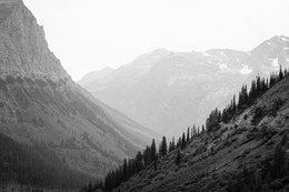 Mount Oberlin and the Going-to-the-Sun Road, with mountains in the background, on a hazy day.