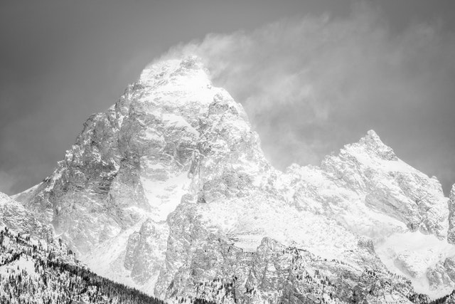 Grand Teton and Mount Owen on a windy day, with snow blowing off from the summit of the Grand.