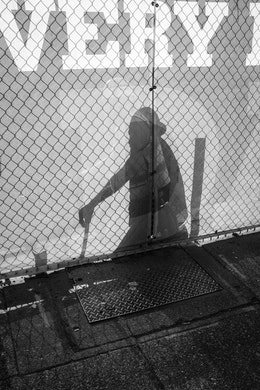 The silhouetted shadow of a construction worker seen through a fence next to the sidewalk in Capitol Hill.