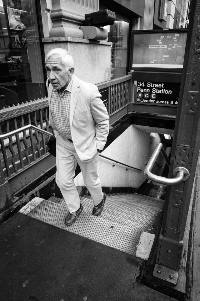 A person in a white suit exiting the 34th Street Penn Station subway station in New York City.