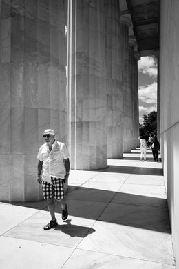 A tourist walking among the columns of the Lincoln Memorial.