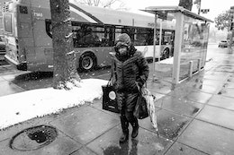 A woman walking past a bus stop on Capitol Hill on a snowy day.