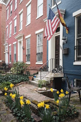 A row house in Capitol Hill, with yellow daffodils in bloom in the front yard, and American and German flags next to the front door.