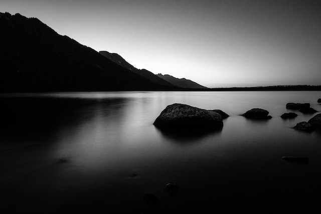 Jenny Lake after sunset. In the foreground, a few big boulders in the water; in the foreground, the Teton Range.