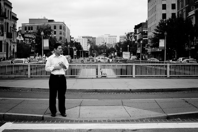A pedestrian waiting to cross the street at Dupont Circle.