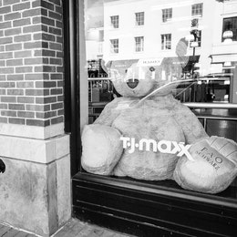 A woman looking at the front window of a TJ Maxx store in Georgetown, which contains a gigantic teddy bear.