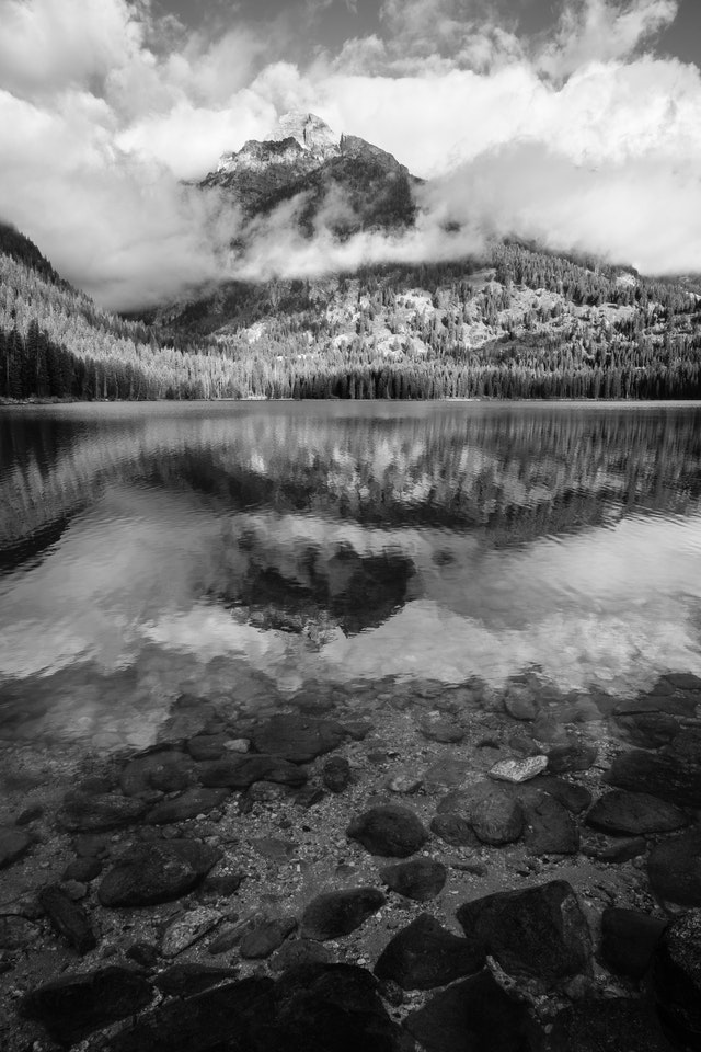 Nez Perce Peak reflected off the surface of Taggart Lake. In the foreground, rocks under the surface of the lake.
