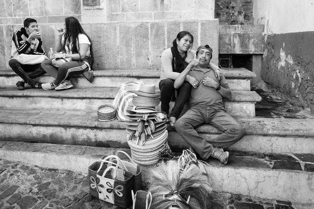A man sitting with his girlfriend, giving a thumbs up.