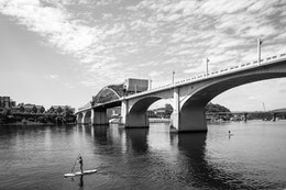 People on paddle boards on the Tennessee river in Chattanooga, with the John Ross Bridge in the background.