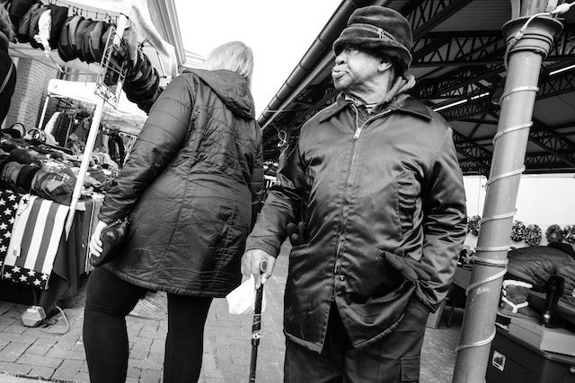 A man with a cane walking past a woman on Eastern Market.
