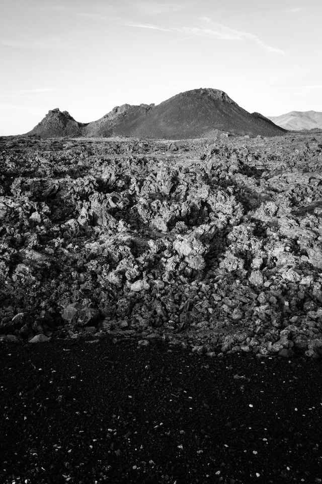 Cinders and a field of ʻaʻa lava in front of a spatter cone.