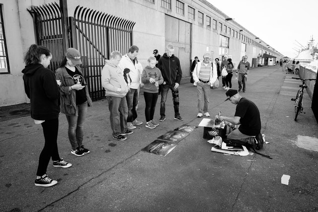 A group of tourists watching a street artist work with spray paint behind the Musée Mécanique in San Francisco.