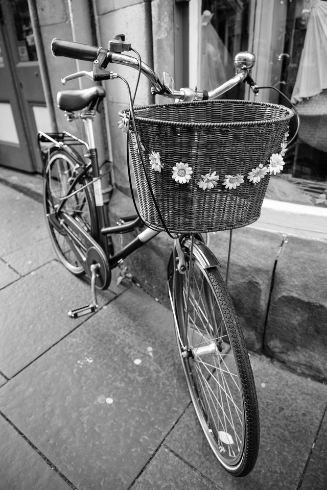 A bike with a basket decorated with flowers on Cockburn Street, Edinburgh.