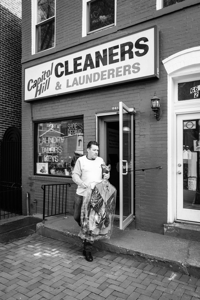 A man walking out of Capitol Hill Cleaners & Launderers with his dry cleaning on Eastern Market.