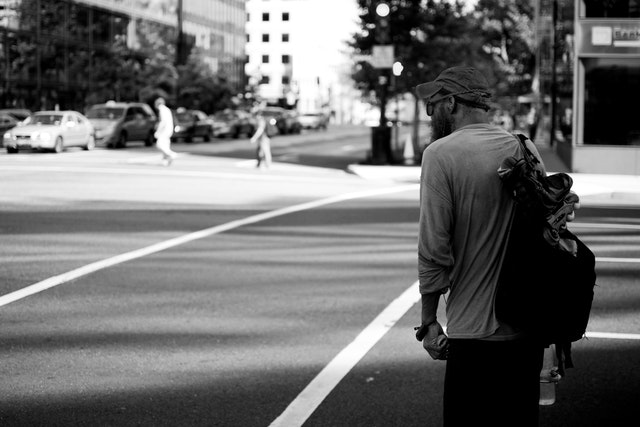 A pedestrian waiting for the light to change near Farragut Square.
