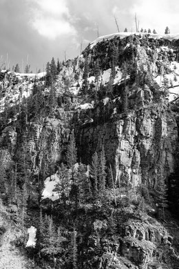 A rocky cliff face covered in snow and trees at Yellowstone National Park.