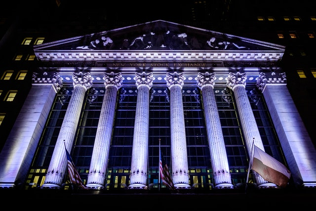 The New York Stock Exchange building, lit up in purple lights at night.