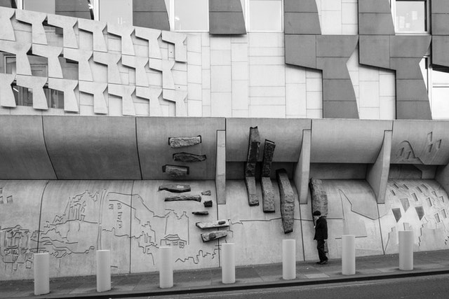 A pedestrian walking in front of the Scottish Parliament Building.