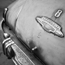 The rear badge of a rusted 1940s Oldsmobile.
