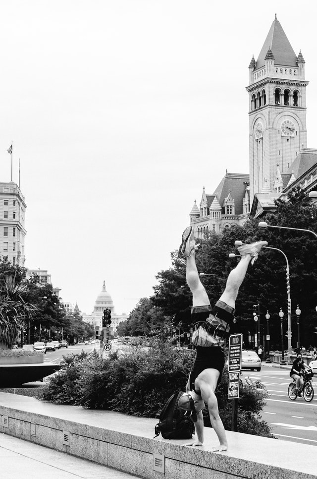 A man doing a head stand at Freedom Plaza in Washington, DC, with the Old Post Office building and the United States Capitol in the background.