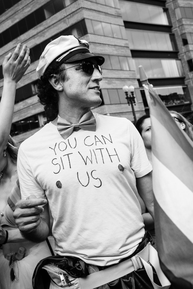 "A person at the Capital Pride Parade, wearing a sailor's hat, bowtie, and t-shirt with cutout nipples and ""you can sit with us"" handwritten on it."