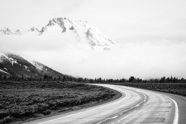The Teton Park Road, wet after a storm. In the background, Mount Moran, partially shrouded in clouds.