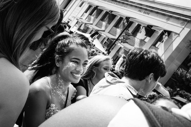 A person in the crowd of the Capital Pride Parade, smiling and covered in glitter.