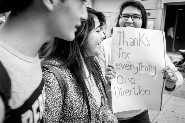 """A woman on the street in Mexico City, holding up a sign that reads """"thanks for everything One Direction""""."""