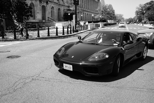 """A Ferrari on Independence Avenue & 1st Street SE, with a DC vanity plate that reads """"IMPEACH""""."""