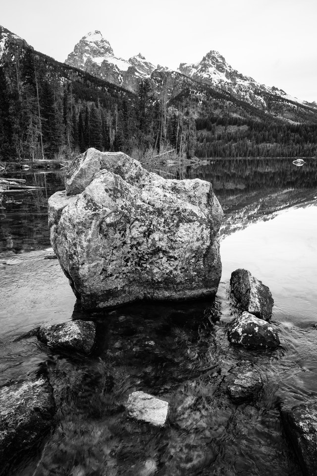 A large boulder in the outlet of Taggart Lake, with water flowing around it. Grand Teton and Teewinot Mountain can be seen in the background.
