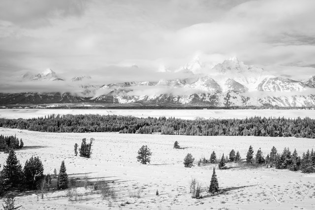 The Teton Range, seen partially hidden by clouds during winter, from the Teton Point turnout.