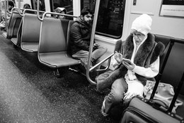 A passenger looking at her phone aboard a Metro train.