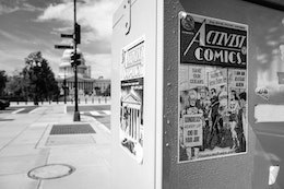 """An """"activist comics"""" poster in front of the United States Capitol."""