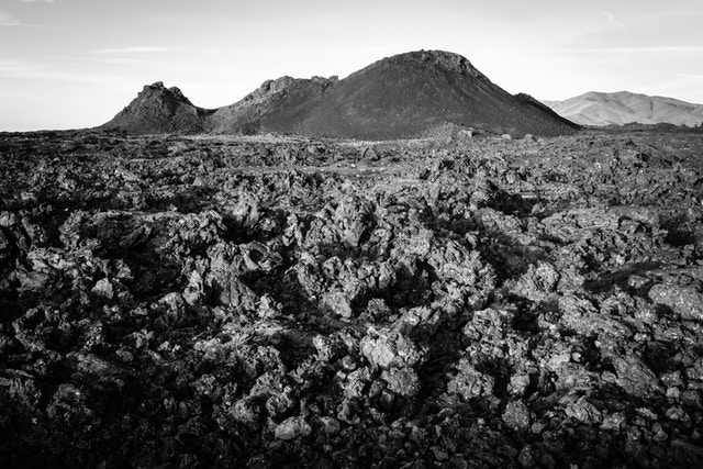 A field of jagged ʻaʻa lava set in front of a spatter cone.