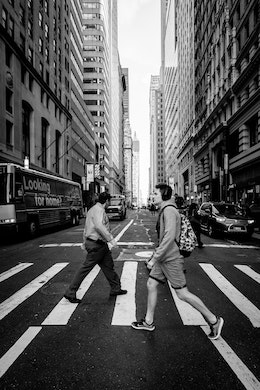 Two pedestrians on a crosswalk on Broadway.