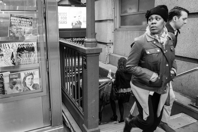 A woman walking out of a subway station.