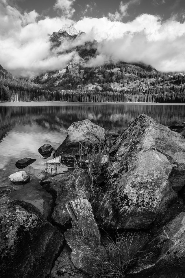 Boulders and grass on the shore of Taggart Lake. In the background, Nez Perce Peak shrouded in clouds and fog.