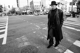 A man wearing a hat, pinstripe suit, and leather overcoat, crossing the street near Dupont Circle.