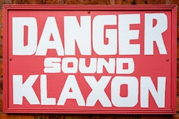 "A red hand-painted sign that reads ""danger sound klaxon""."