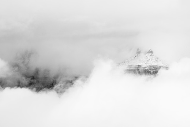 A distant butte on the North Rim seen through the clouds from the Grand Canyon Village during a snowstorm.