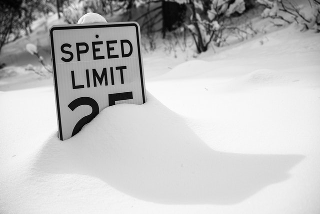 A speed limit sign partially covered in snow.