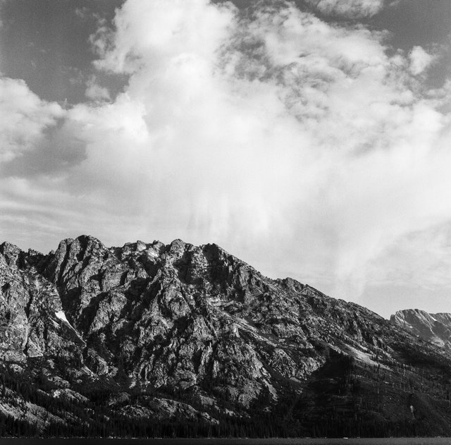The Tetons, seen under clouds from Jenny Lake.