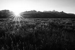 The sun setting behind the Teton range.