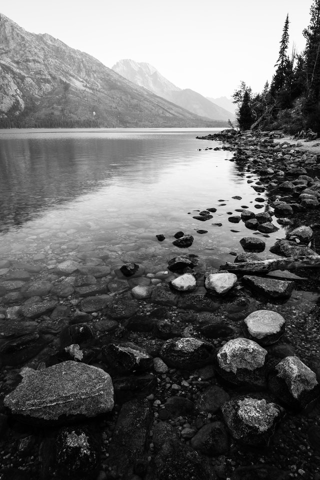 Rocks on the shore of Jenny Lake. Mount Moran can be seen in the distance.