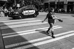 A woman smiling and crossing the street while a sheriff SUV drives past her, on Pine Street in Seattle.