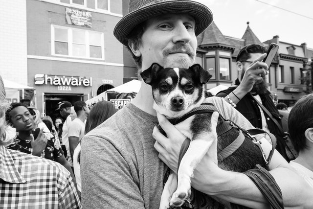 A man holding a cute dog at the H Street Festival in Washington, DC.