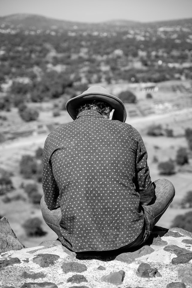 A tourist sitting at the edge of the Pyramid of the Sun in Teotihuacán.