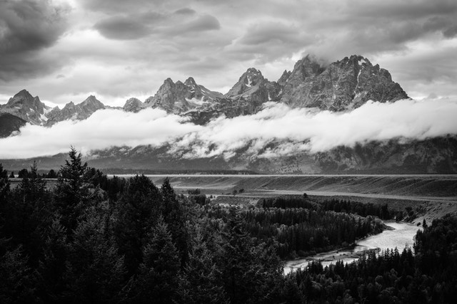 The Teton range on a stormy afternoon, from the Snake River Overlook. Grand Teton is hidden in the clouds, and a band of clouds is floating along the middle of the range.