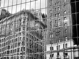Buildings reflected on glass near Herald Square.