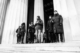A group of people looking at the view from the top of the stairs of the Lincoln Memorial.